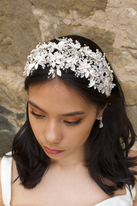 Black hair model wears a white leaves bridal headband that is wide with a stone wall behind her