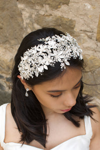 Black hair model looks down wearing a wide bridal headpiece with many leaves. Stone wall is behind