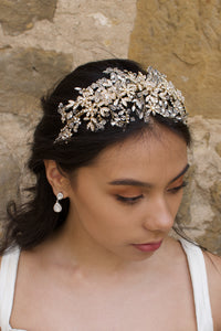 A model with dark hair wears a wide golden headband on the front of her head