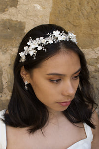 Dark hair model wears a headband of ceramic flowers  and pearls with a wall background