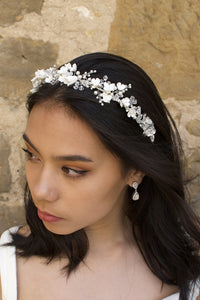 A bride with black hair wears a headband of ceramic flowers and clear crystals with a wall background
