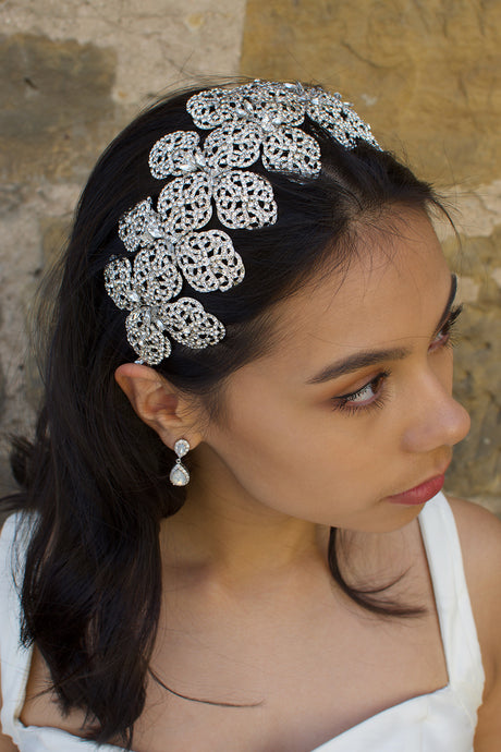 A dark hair model wears a very wide silver headband with a stone wall backdrop