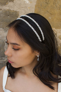 Dark hair model wears a two row bridal headband with a sandstone wall behind