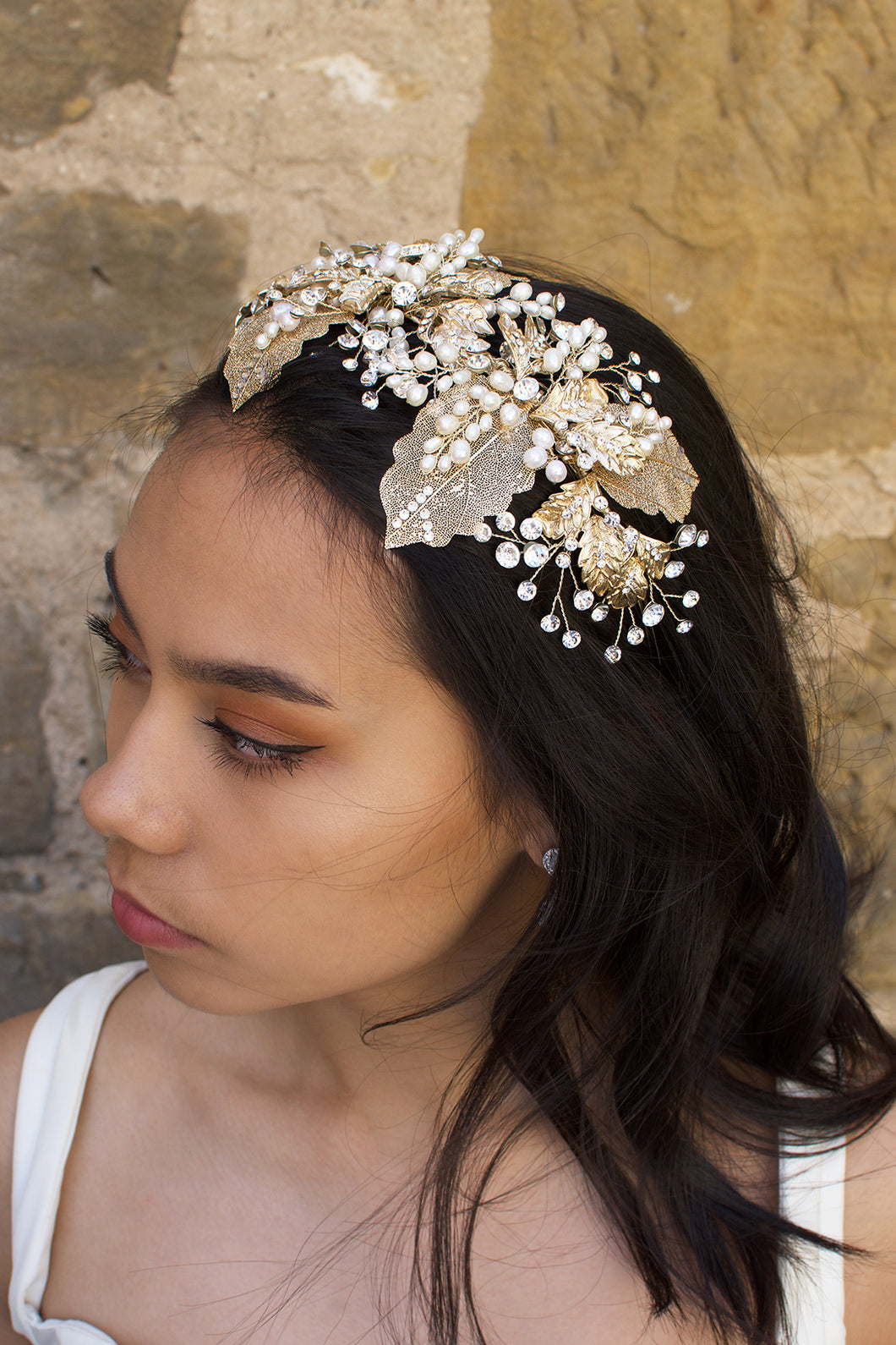 A wide gold headband worn by a dark hair bride with a stone wall background