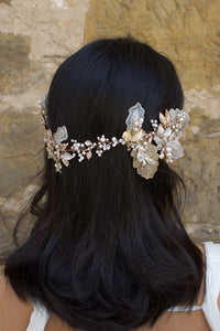 A dark haired model wears a Bridal Vine in Silver, Gold and Rose Gold with a background of a stone wall
