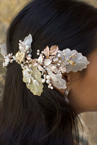A dark haired model with hair down wears a Bridal Vine in Silver, Gold and Rose Gold with a background of stone