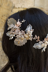 A dark haired model with hair down wears a Bridal Vine in Silver, Gold and Rose Gold with a background of a stones
