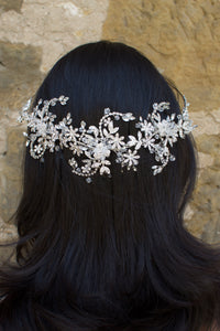 Silver and crystal headband worn at the back of a models head with a stone wall background