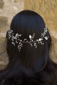A silver pearl bridal vine with leaves worn by a dark haired model on the back of her head