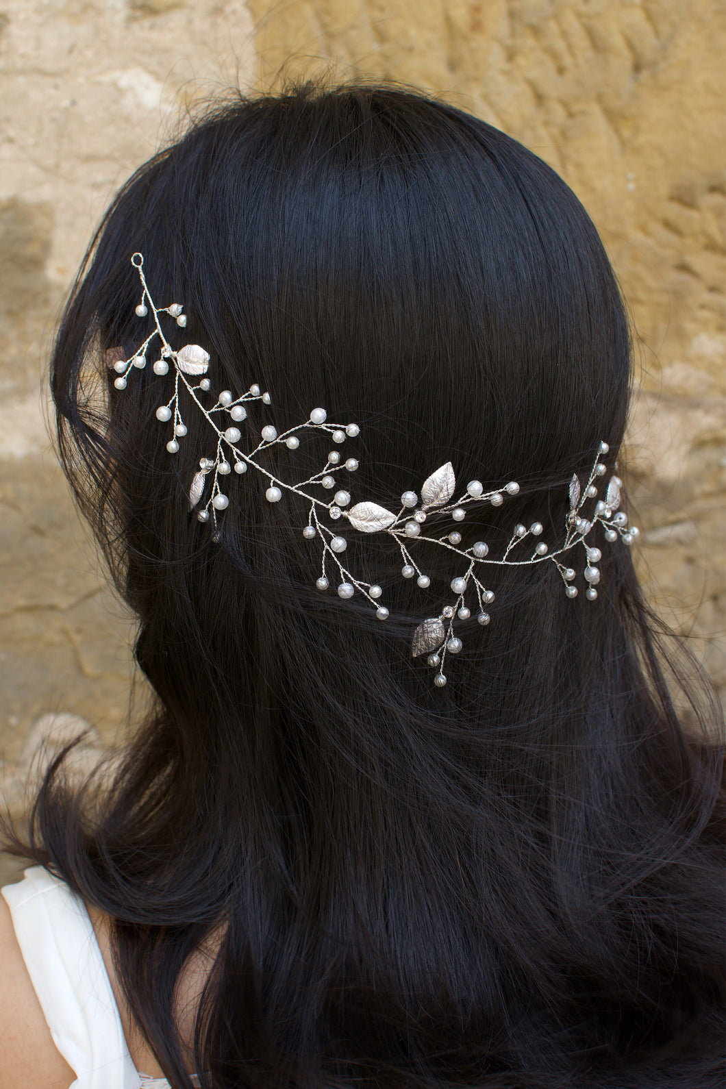 A black hair model wears a silver bridal vine on the back of her head with leaves and pearls