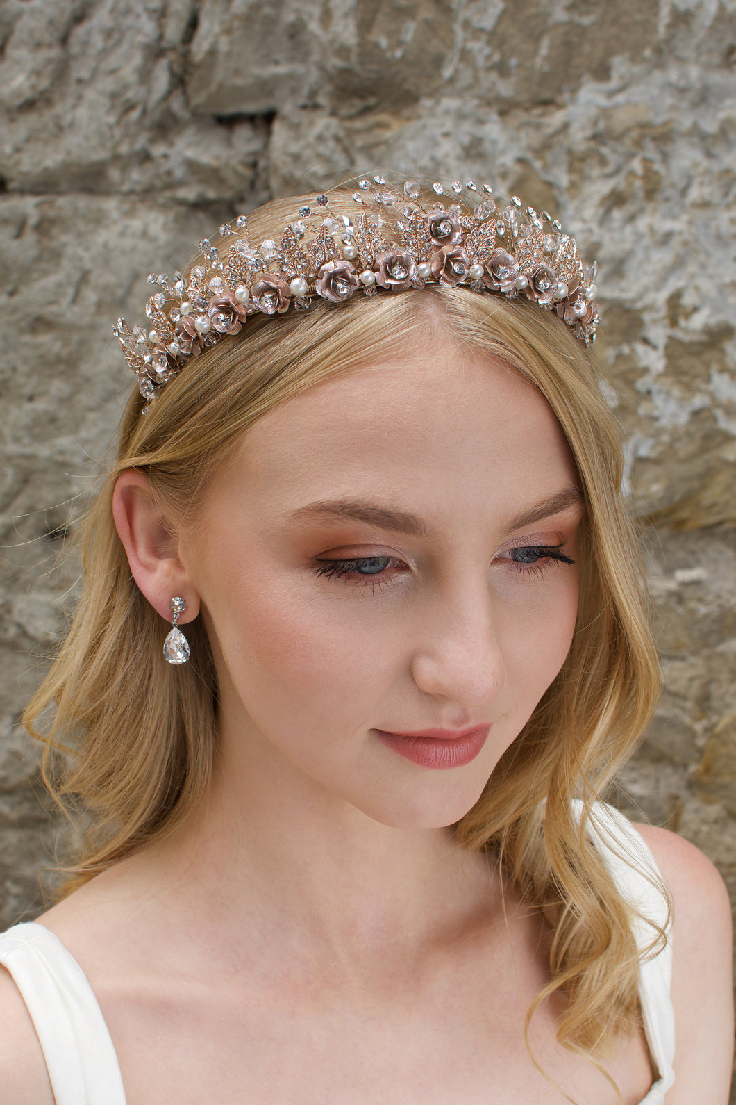 A Rose Gold Flowers and pearls wide tiara worn by a blonde bride with a stone wall background.