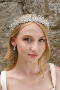 A Soft Silver Flowers and pearls wide tiara worn by a blonde bride with a stone wall background.