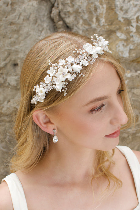 A blonde Bride wears a headband of ceramic flowers and pearls with a stone wall background