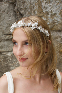 Smiling Blonde Bride wears a headband of ceramic flowers with a stone wall background