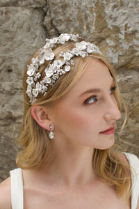 Blonde model looks up wearing a 2 row flowers headband with a stone backdrop