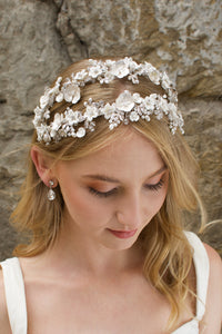 Blonde hair model looks down wearing a twin row bridal headband of flowers with a stone background