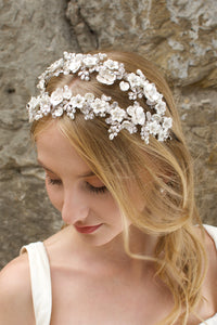 Blonde bride wears a double row flower headband with a stone wall background