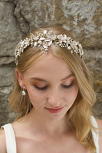 Load image into Gallery viewer, A model Bride with blonde hair wears a gold bridal crown at the front of her head with a stone wall behind