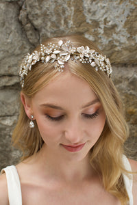 A model Bride with blonde hair wears a gold bridal crown at the front of her head with a stone wall behind