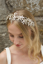Load image into Gallery viewer, Blonde model wears a very pale gold bridal headband with a stone wall background