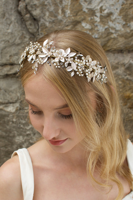 Blonde model wears a very pale gold bridal headband with a stone wall background