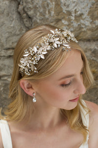 Blonde hair Bride wears a Champagne Gold wide bridal headband with leaves with a stone wall background