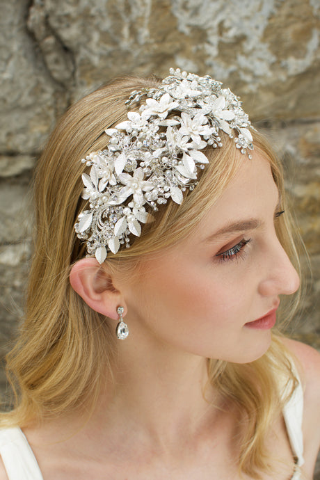 Blonde model wears a silver leaf headband thats wide she wears an earring and the background is a stone wall