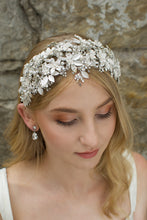 Load image into Gallery viewer, Model facing the camera wears a wide silver leaves bridal headband and the background is an old stone wall.