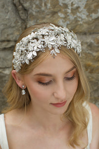 Model facing the camera wears a wide silver leaves bridal headband and the background is an old stone wall.