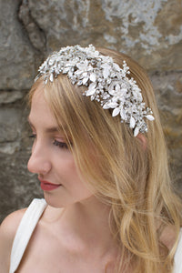 A bride with blonde hair wears a wide silver flowers headband with leaves