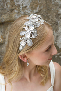 Bridal headband with Lace leaves and white flowers worn by a blonde bride in front of a stone wall.