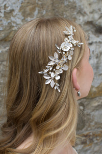 A Comb with different flowers and leaves in Pale Gold with pearls sits on the head of a blonde model bride