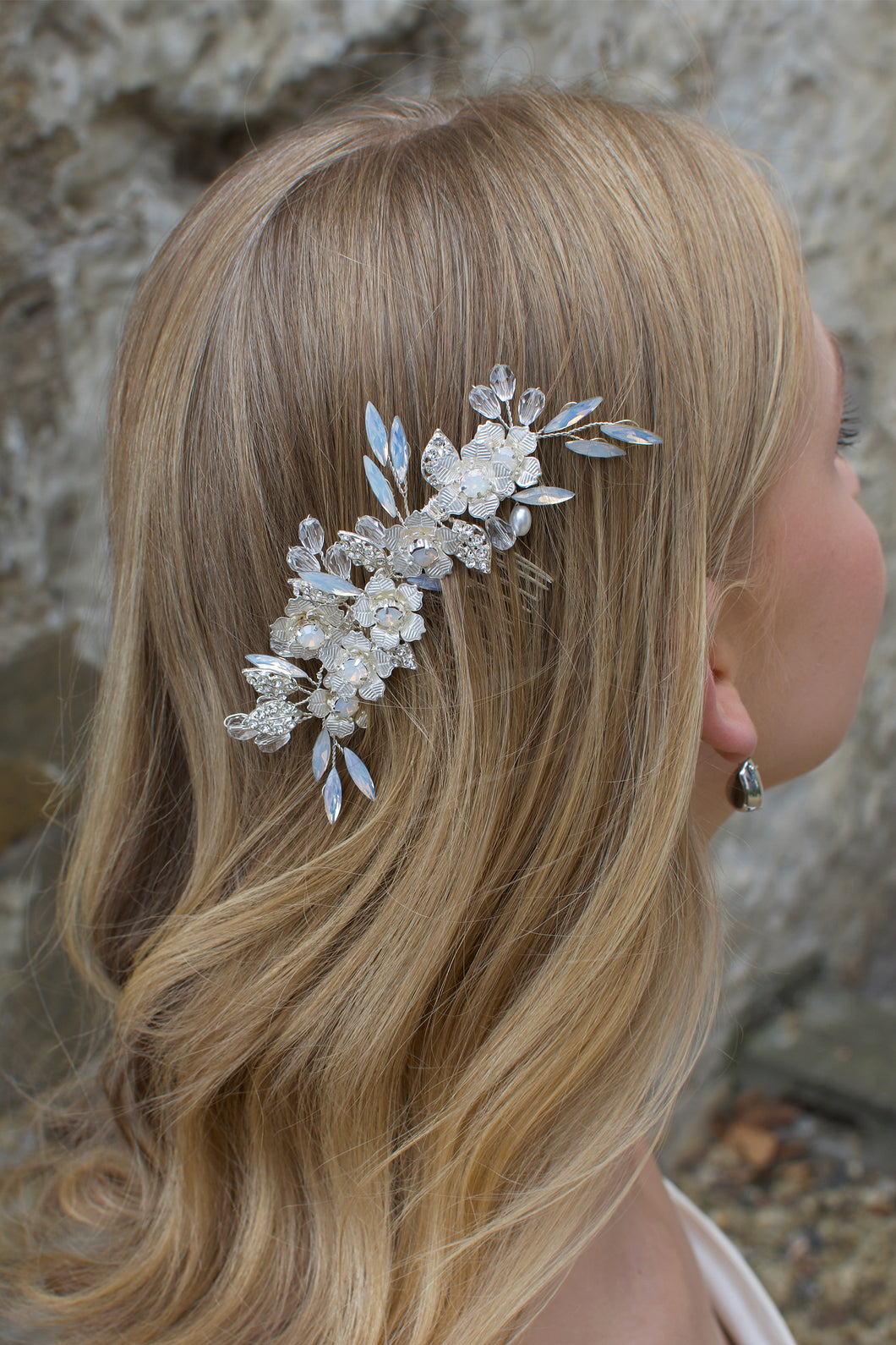 Long Blonde hair Model Bride wears a small white opal comb on the side of her head. There is a stone wall background