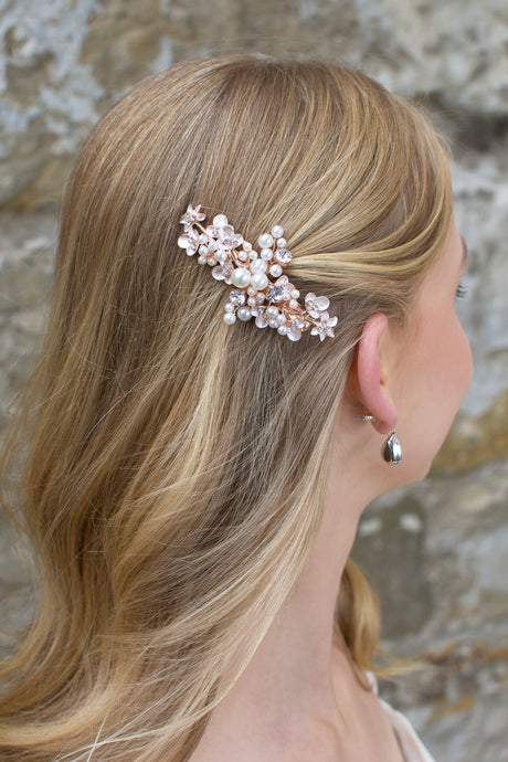 Blonde hair bride wears a pearl encrusted small side clip on rose gold with a stone wall behind.
