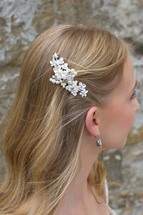 Blonde hair bride wears pearl and silver bridal side comb on the side of her head.