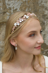 Blonde Bride wearing a pale Rose Gold headband with flowers with a stone background