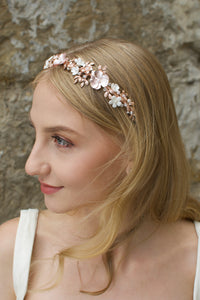 Blonde haired Bridal model wearing a pale rose gold bridal headband with stone background