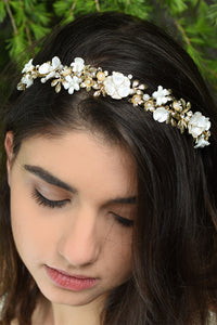 White Flowers and gold leaves headband worn at the front of a dark hair model's head with pine tree background