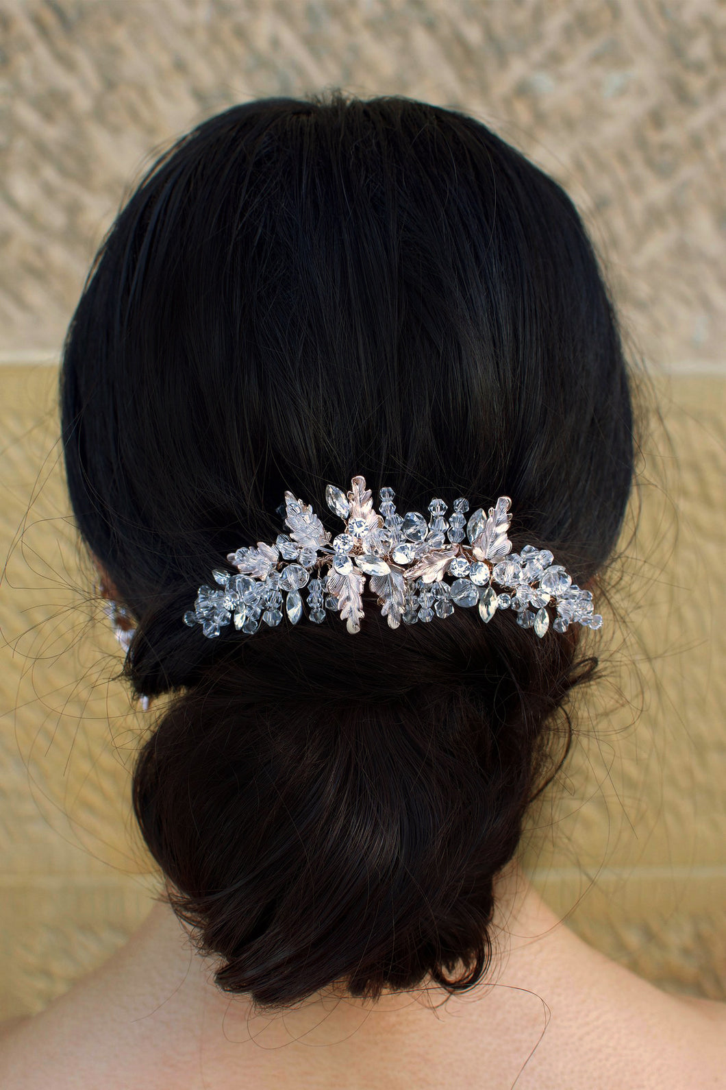 Crystals and Rose Gold clip worn on black hair at the back of a model's head with metal leaves.