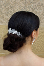 Load image into Gallery viewer, Clear Crystal and tiny leaves Bridal Side Comb worn by a dark hair model at the back of her hair with a stone wall background