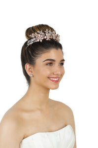 Rose Gold Crown worm by a smiling bride in an ivory bridal gown with a white background