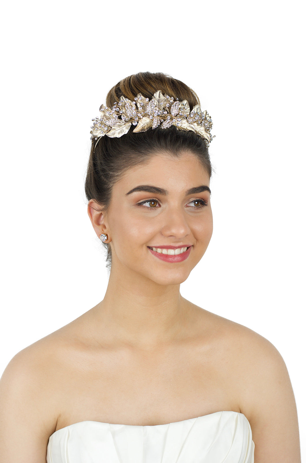 Model wearing a pale gold crown around her up style hairdo with a white background.