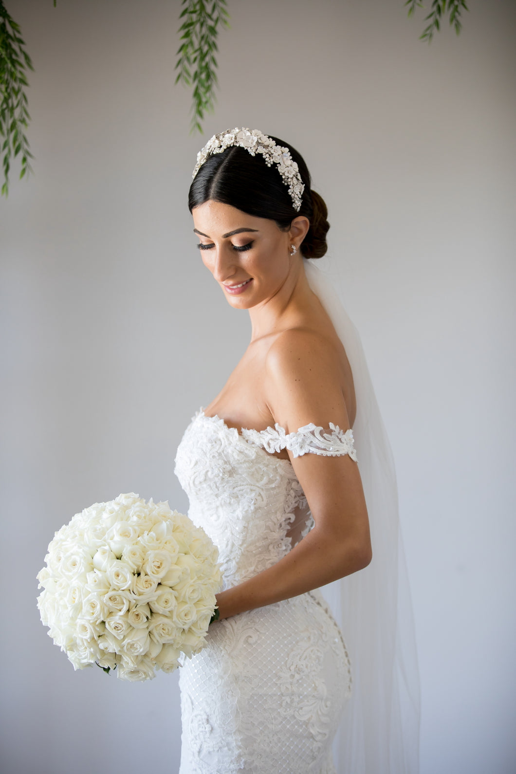 A bride wears a headband of ceramic flowers on her dark hair. There are green leaves in the background