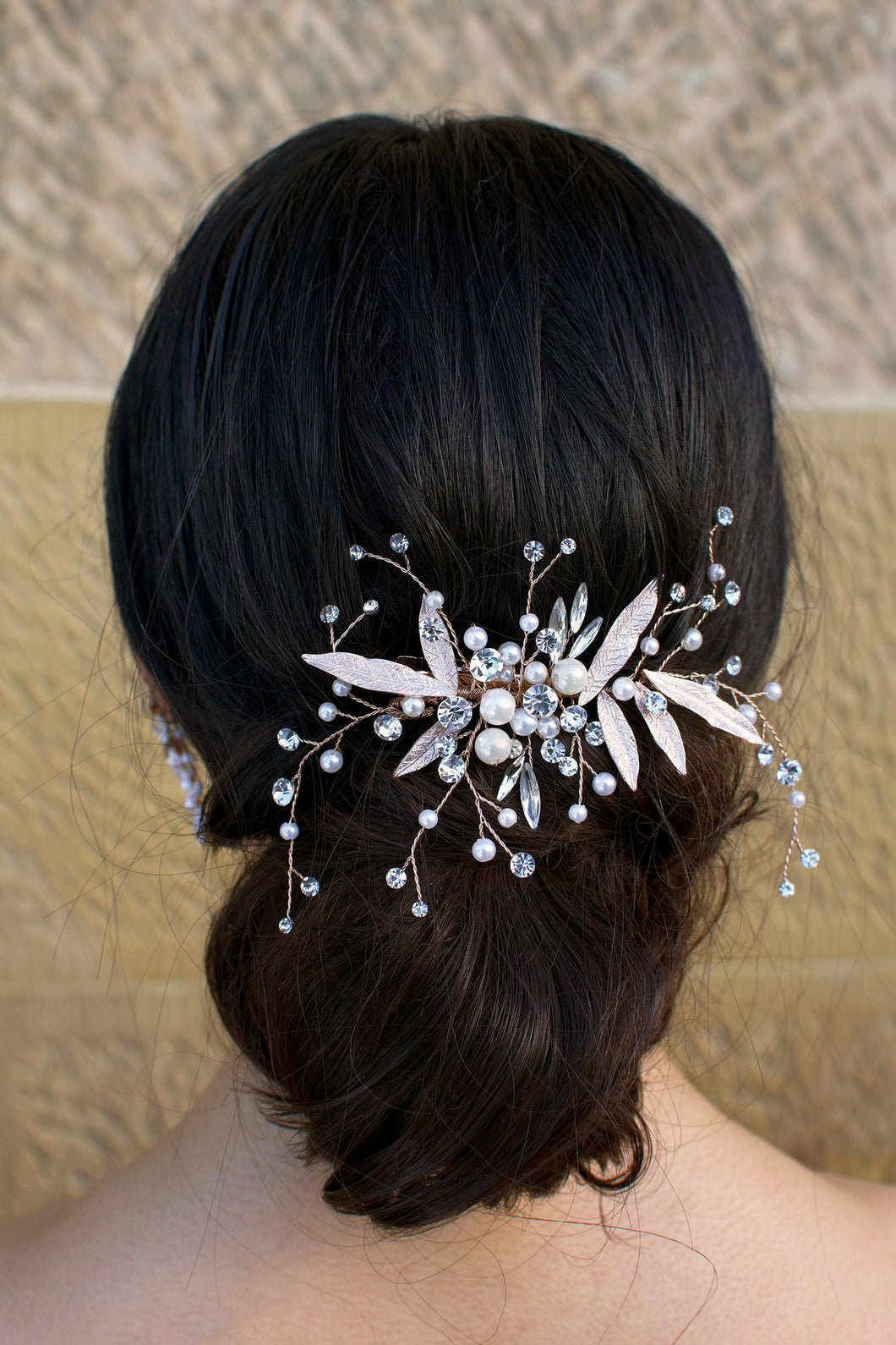 dark hair model wears a comb with pearls and leaves at the back of her head