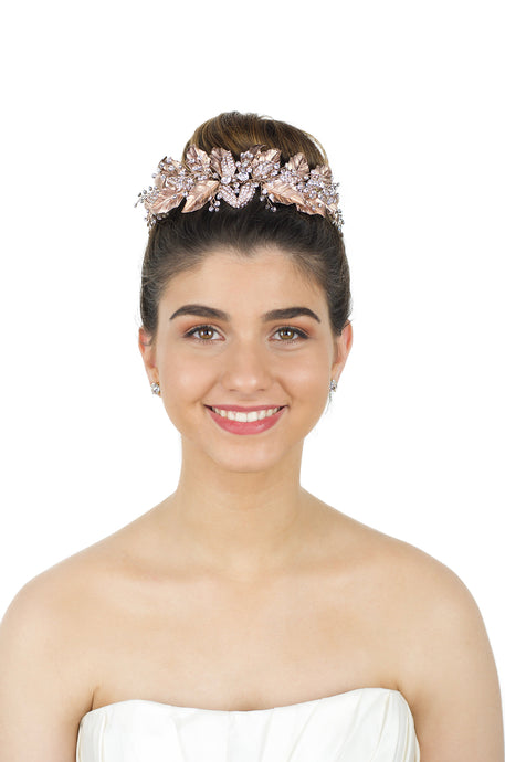 Smiling Bride wears a Rose Gold Tiara in her up styled bridal hairdo with a white background