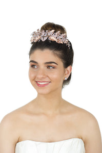 Bride wears a Rose Gold Leaf Crown at the front of her head against a white background