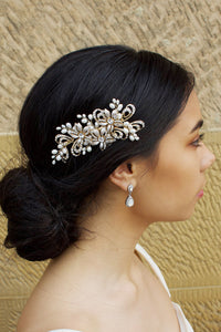 Model with dark hair wearing a small gold side comb in her hair. There is a stone wall behind her