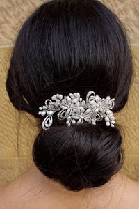 A bride wears a soft silver and pearl comb on top of a hair bun at the back of her head