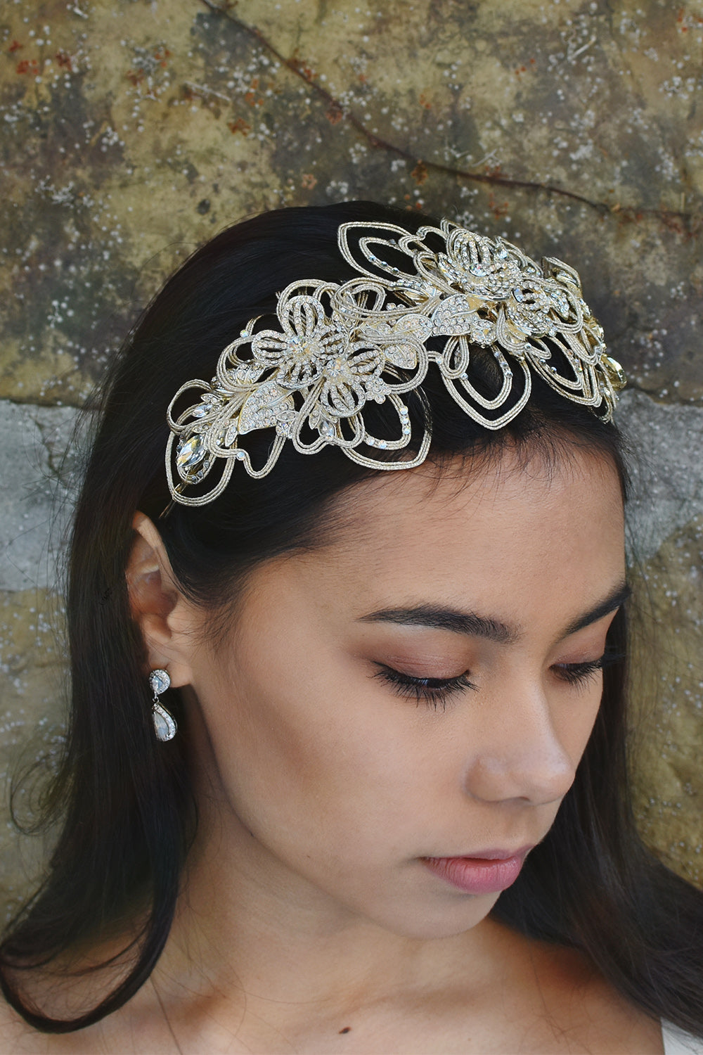 Dark haired model wearing a matt gold bridal headband at the front of her head. There is a stone wall behind her.