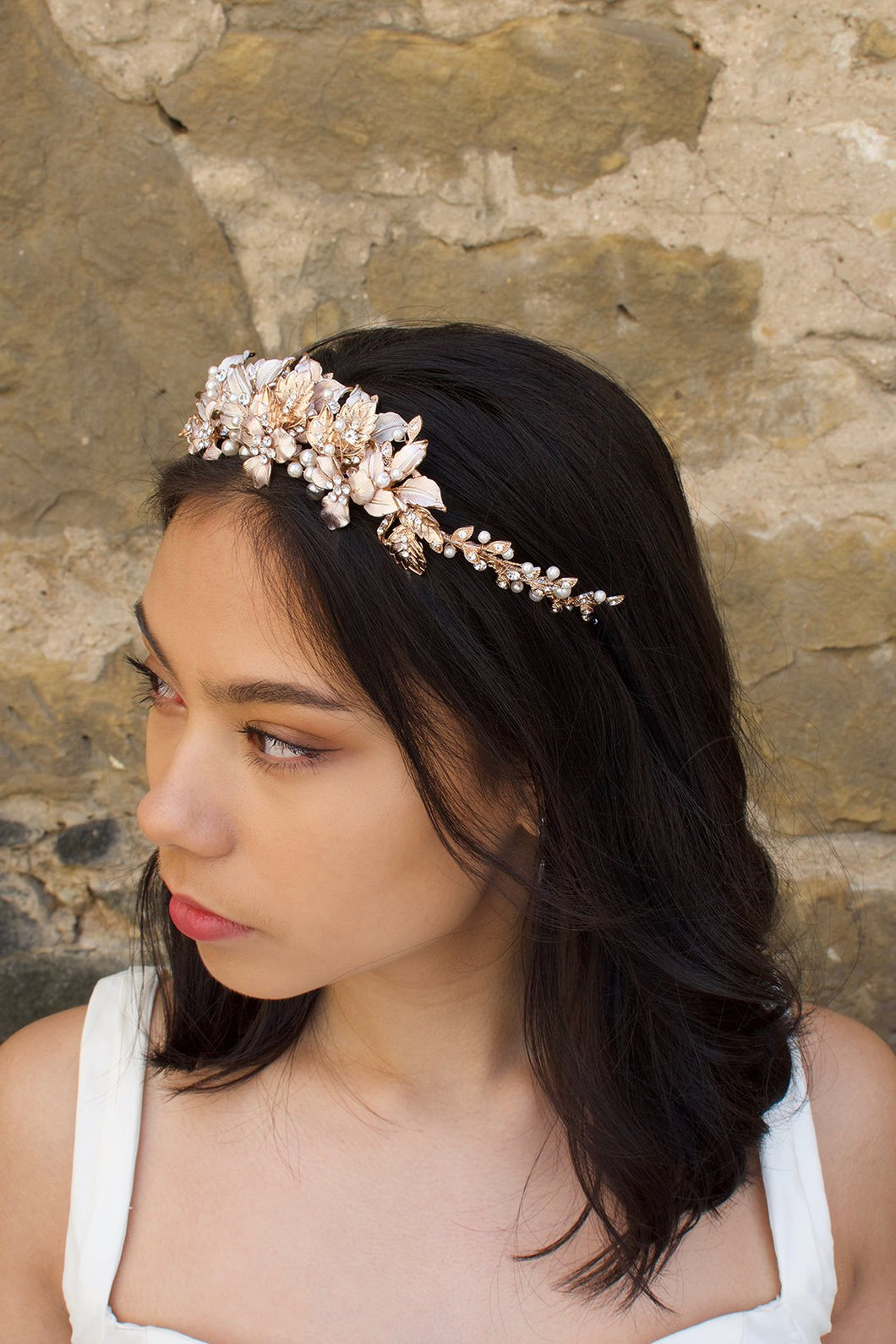 Black haired model wears a pale rose gold and pearl low bridal headband
